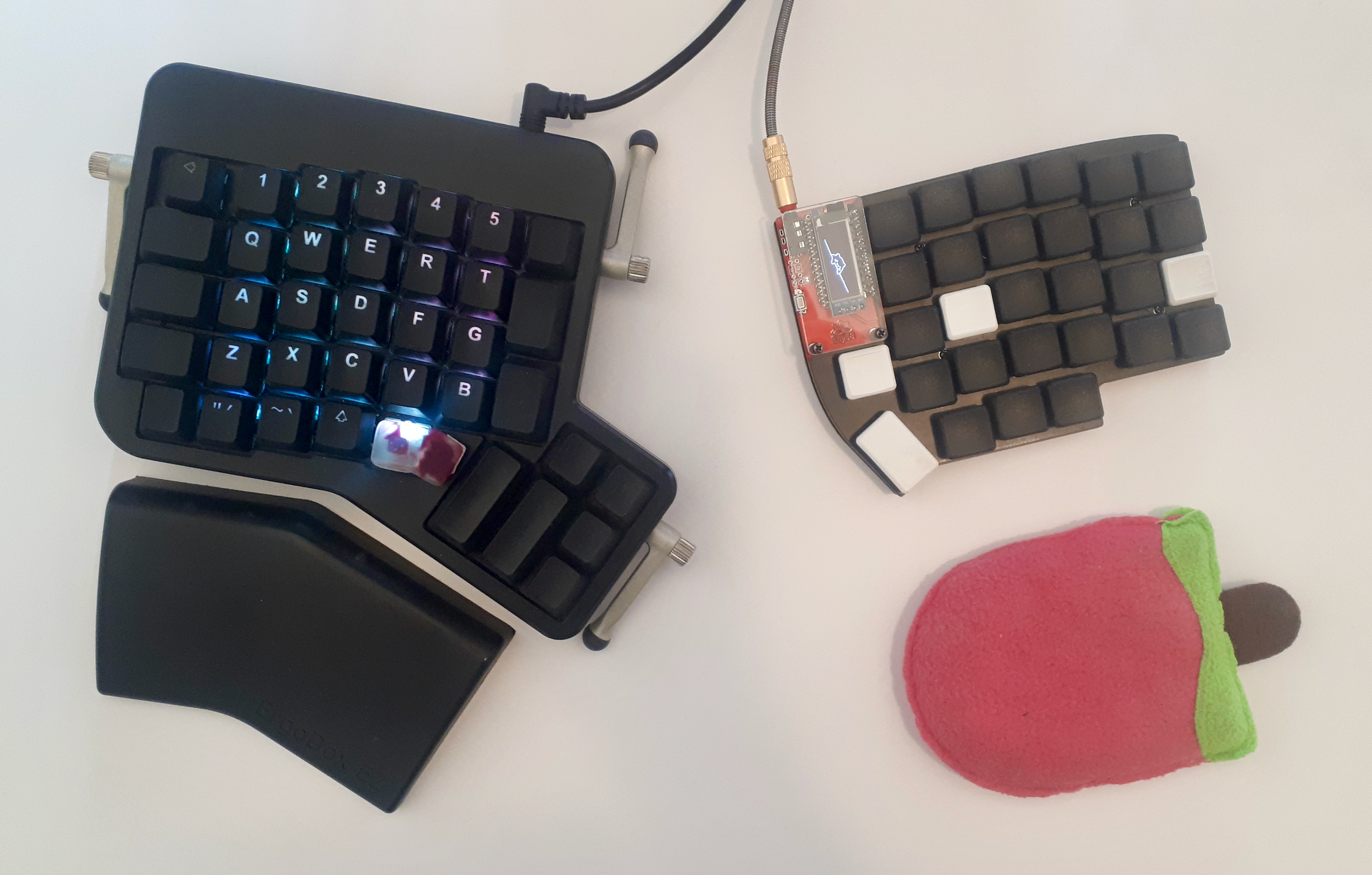 Lily58 next to an Ergodox. Lily58 is smaller.
